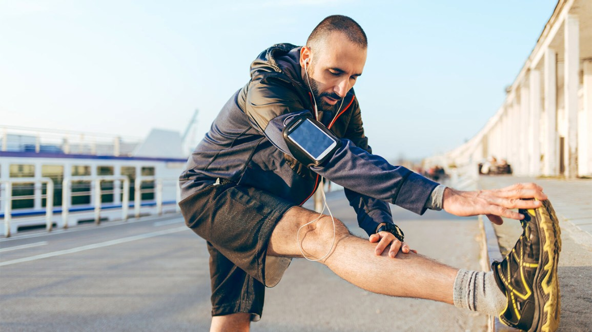A man stretches his legs before starting a run in an outdoor urban area.