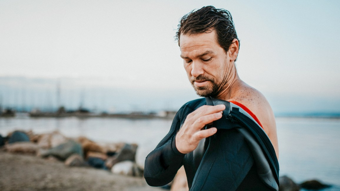 man putting on wet suit outdoors beside water