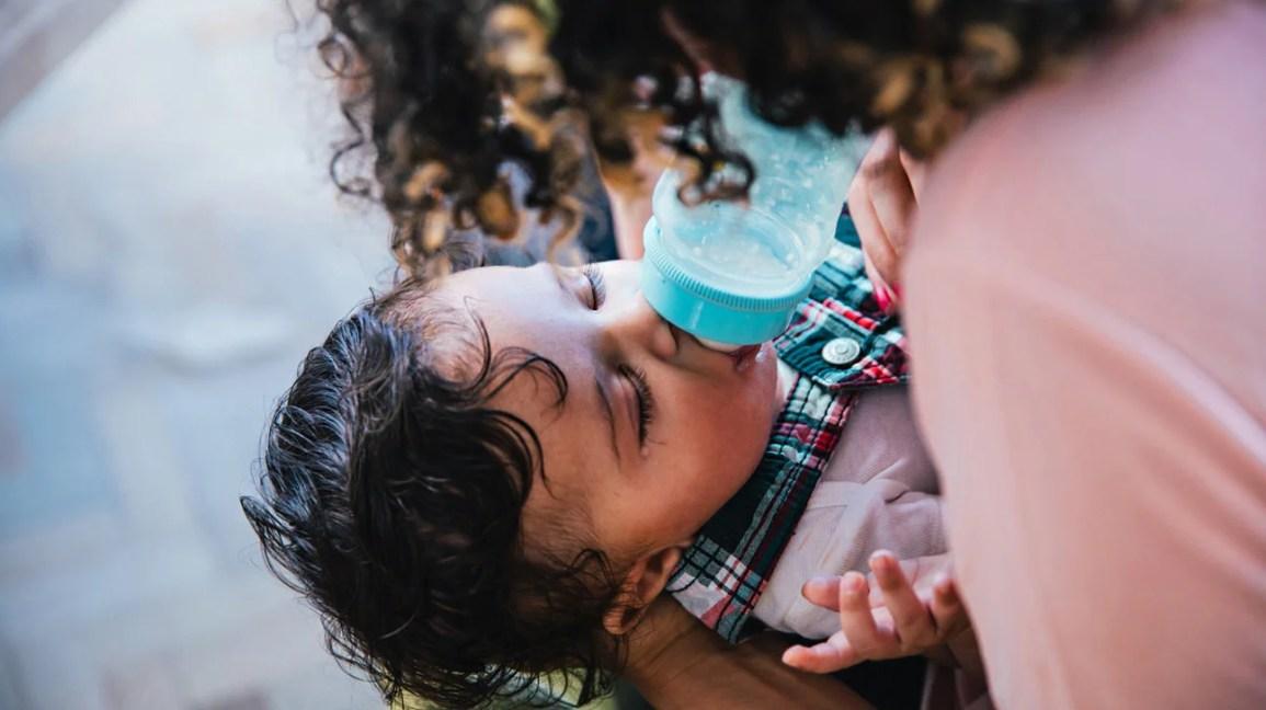 pai alimentando bebê com mamadeira