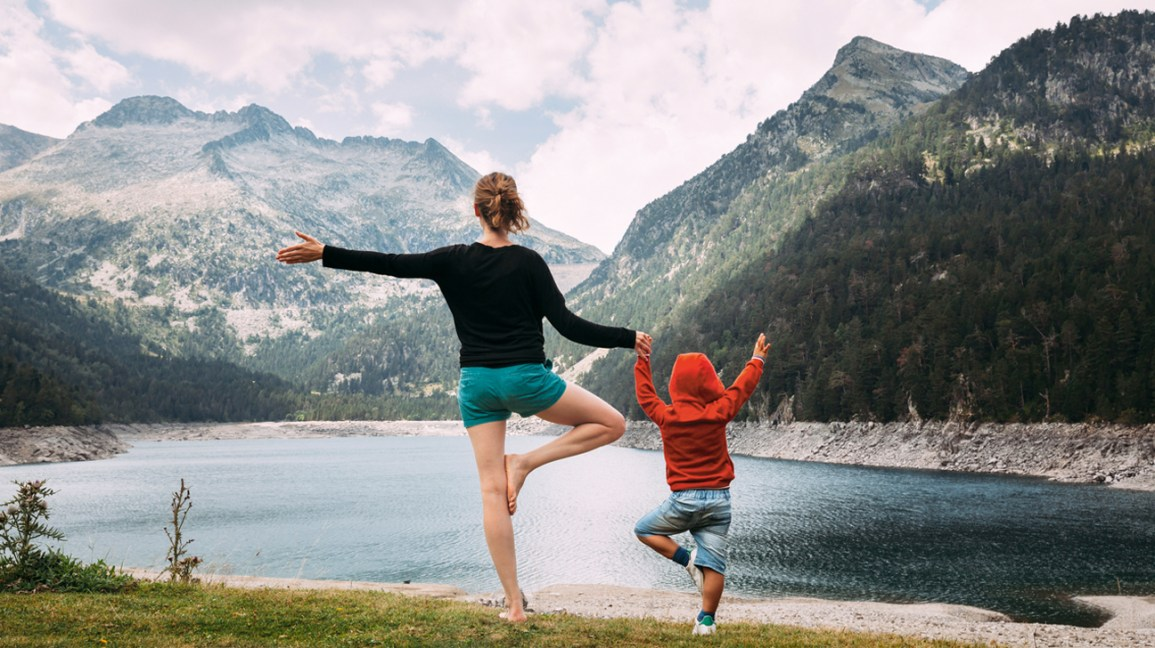 woman and child do yoga by a lake