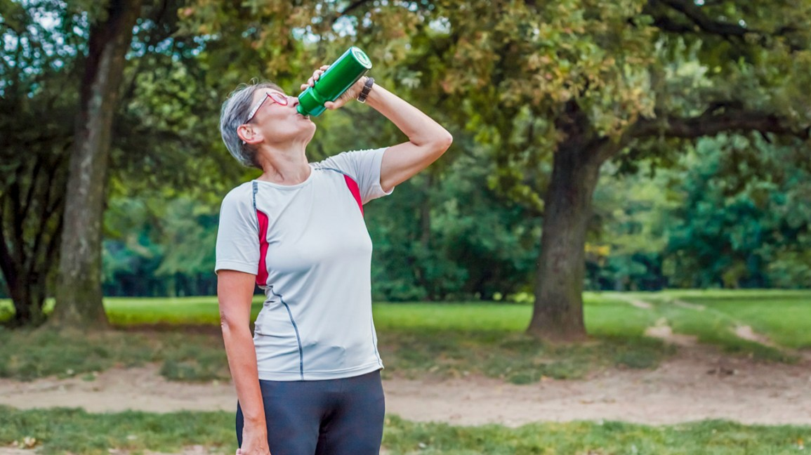 A senior woman in running gear drinks water from a sports bottle while on a trail in the park.