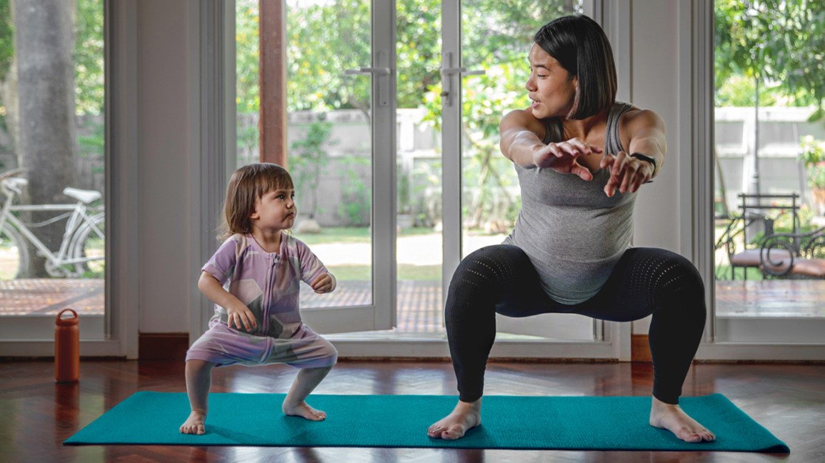 Pregnant mom doing squats with daughter