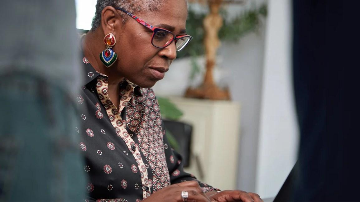 mulher de óculos olhando para uma tela de computador com as mãos colocadas no teclado