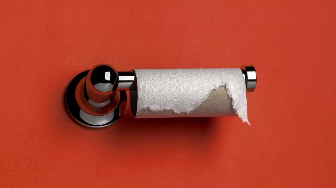 empty toilet paper roll against red wall