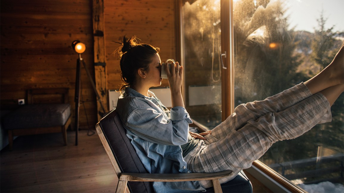 Woman in a cabin relaxing alone drinking coffee