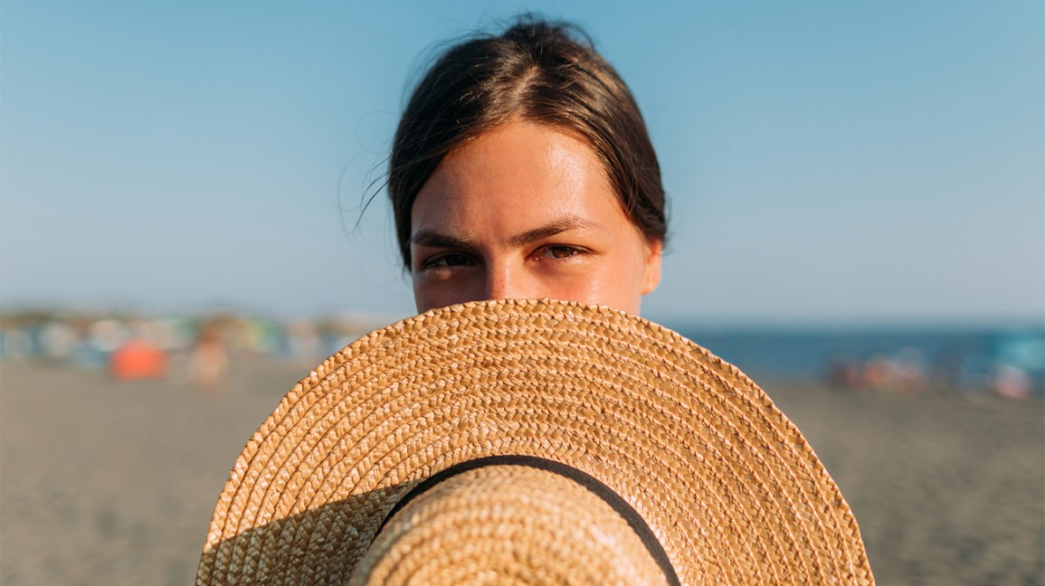 A woman in full sunlight holds a hat in front of her face to help shade her from the sun.