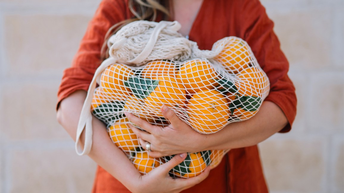Woman carrying a net full of oranges