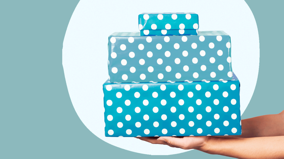 A hand holding presents wrapped in polka dot wrapping