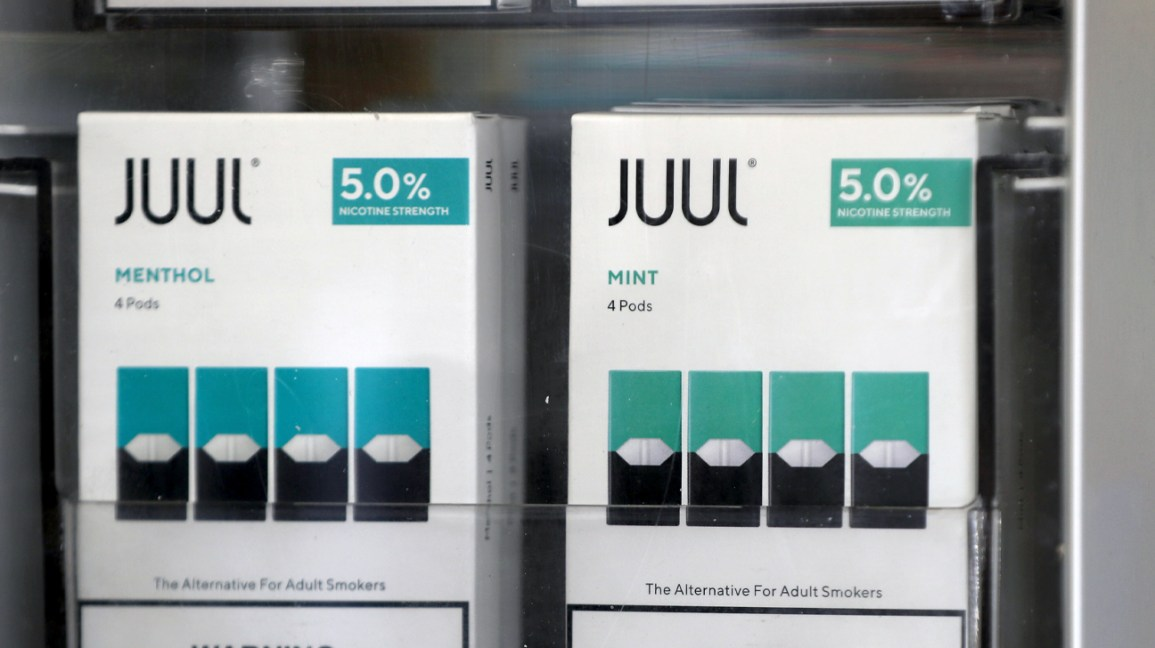 JUUL pods displayed on a store shelf.