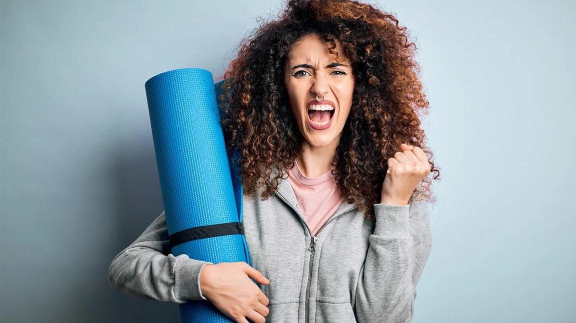 mulher zangada segurando tapete de ioga