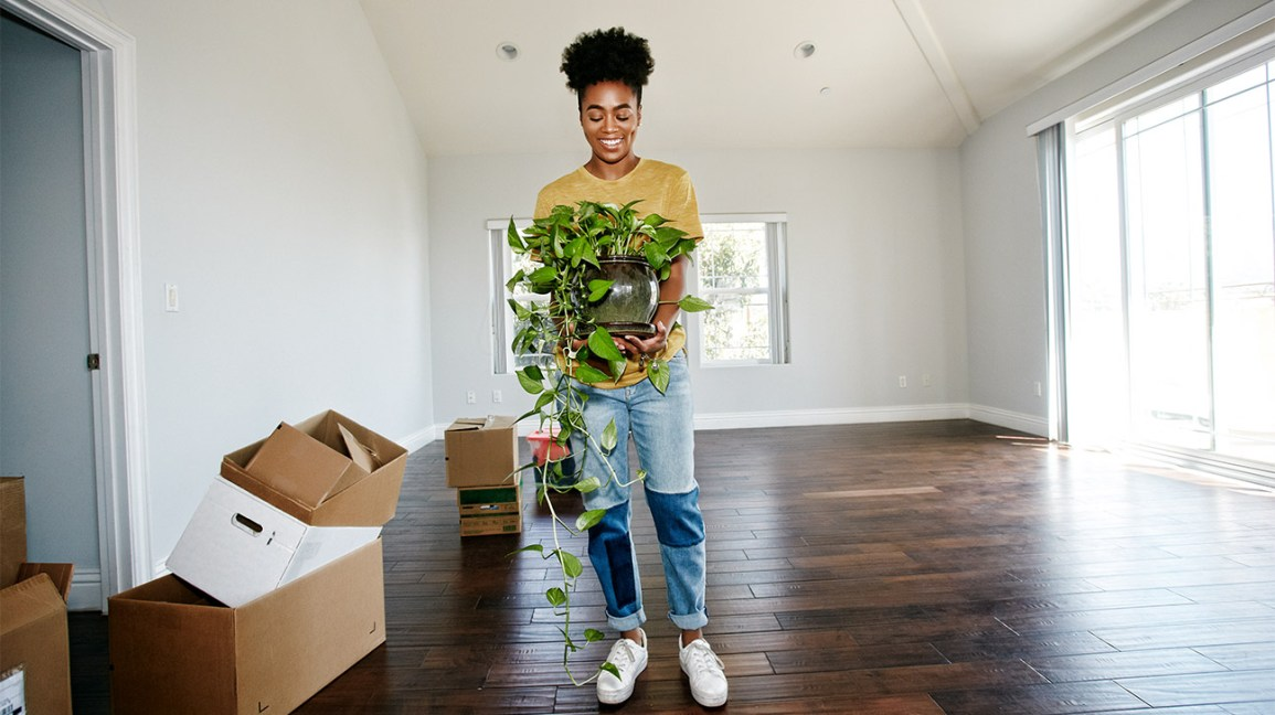 woman holding plant in empty apartment