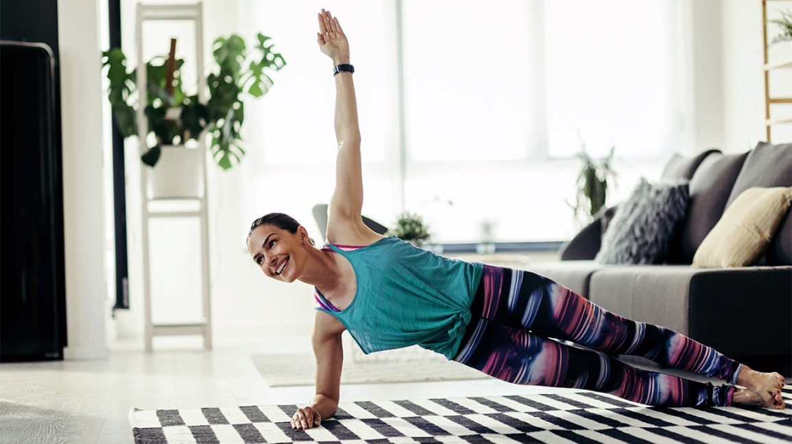 person wearing a turquoise tank top and pink and blue leggings performing a side plank in their living room