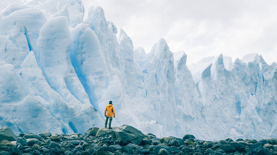 person standing on rocks looking up at huge glaciers