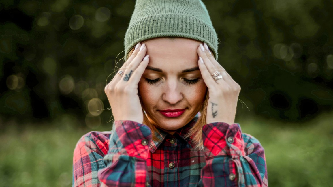 A woman wearing a beanie and flannel shirt closes her eyes with her fingertips pressed against the sides of her head.