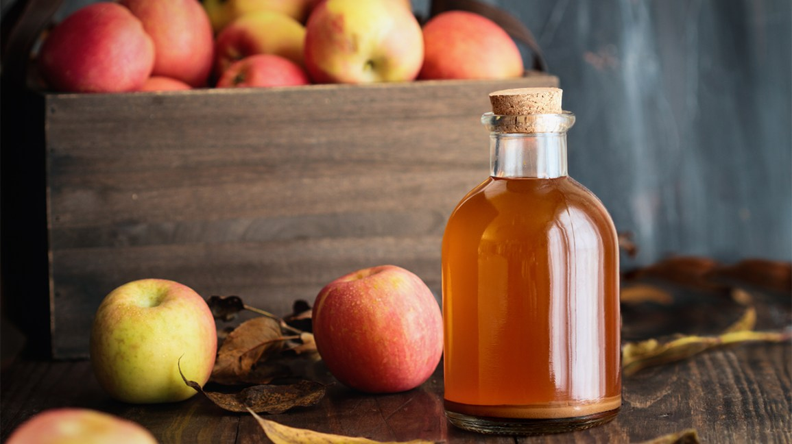 Fresh apples and a bottle of apple cider vinegar