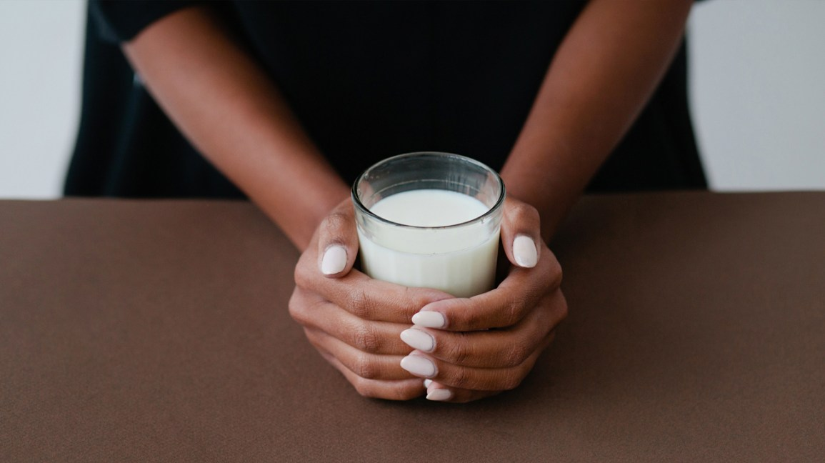 Hands holding a glass of milk