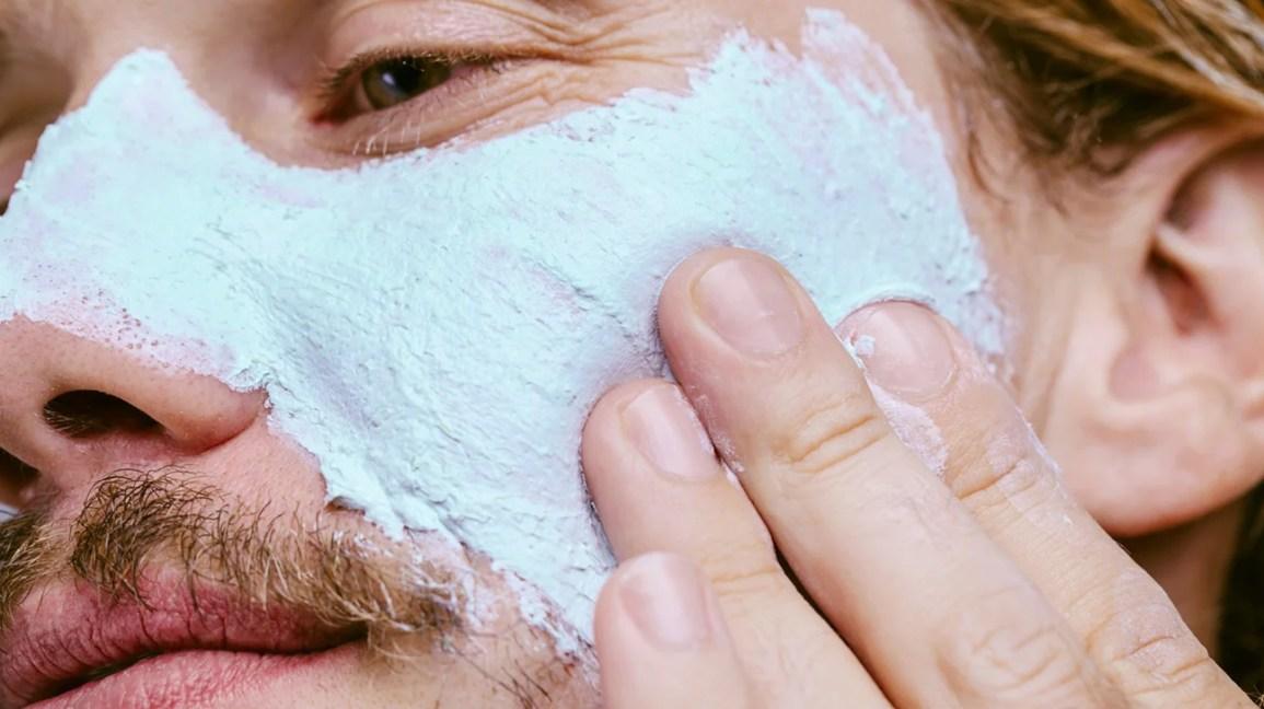 close-up de uma pessoa aplicando uma máscara de lama azul claro na bochecha