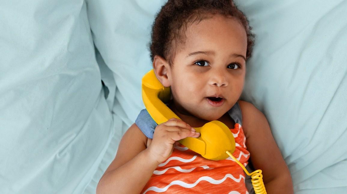 criança com olheiras segurando um telefone