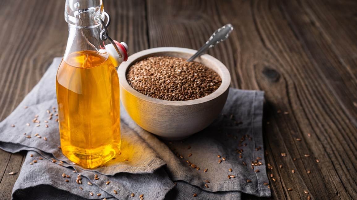 A bowl with flax seeds and a small glass bottle with flaxseed oil