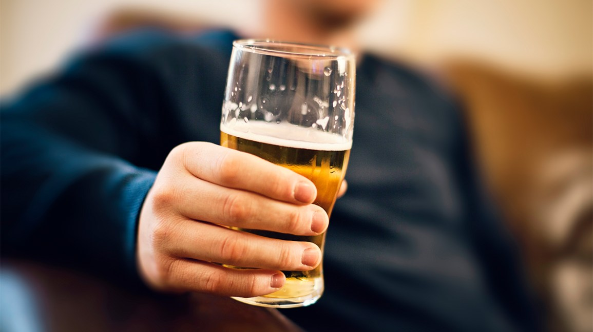 closeup of hand grasping glass of beer