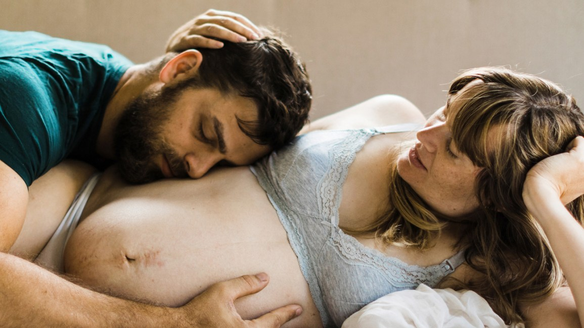 Man and pregnant woman cuddling in bed