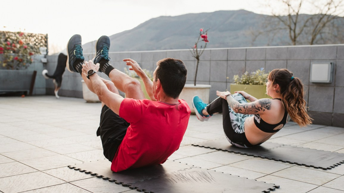 a man and woman do crunches with hands and feet lifted off the ground