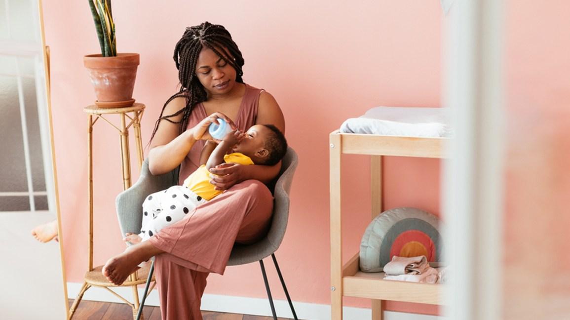 mother bottle feeding baby in nursery