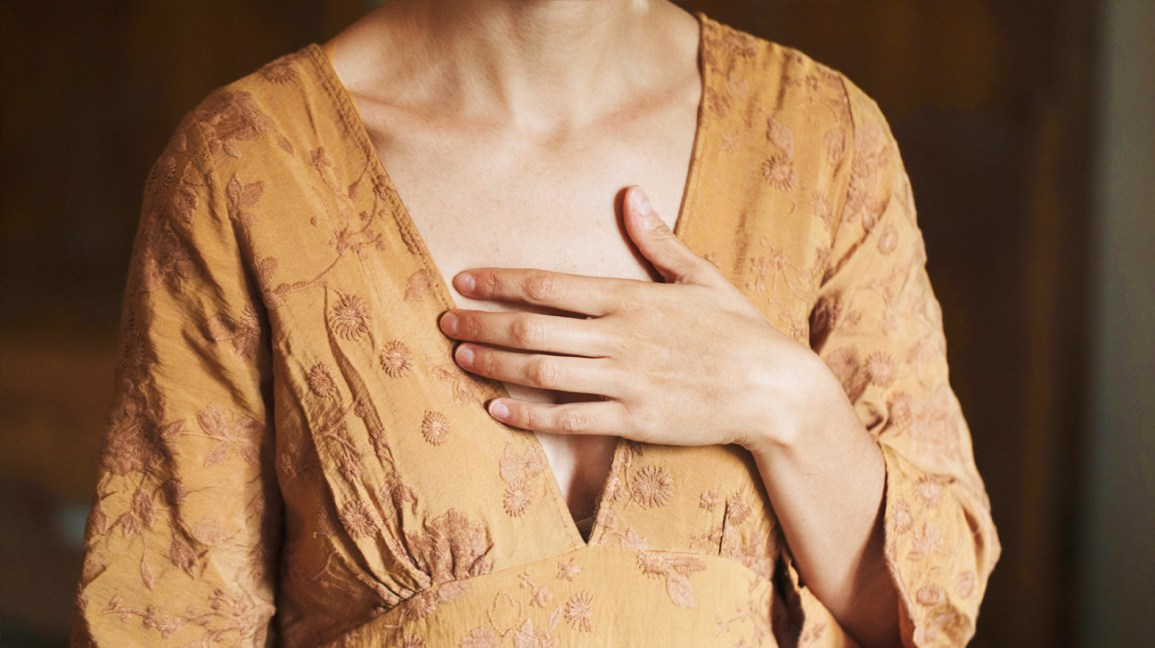 Woman with hand on her chest