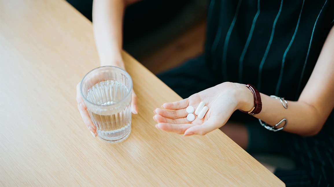 person taking pills with a glass of water