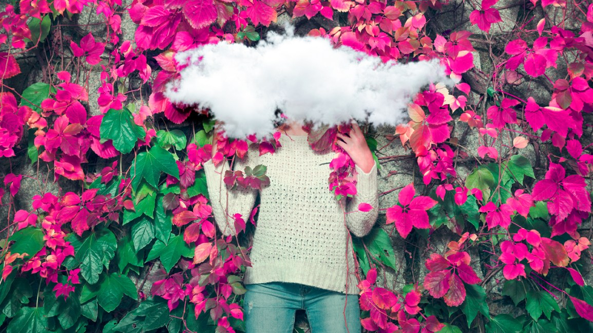 woman standing in flowers with a cloud over her face in a dream state