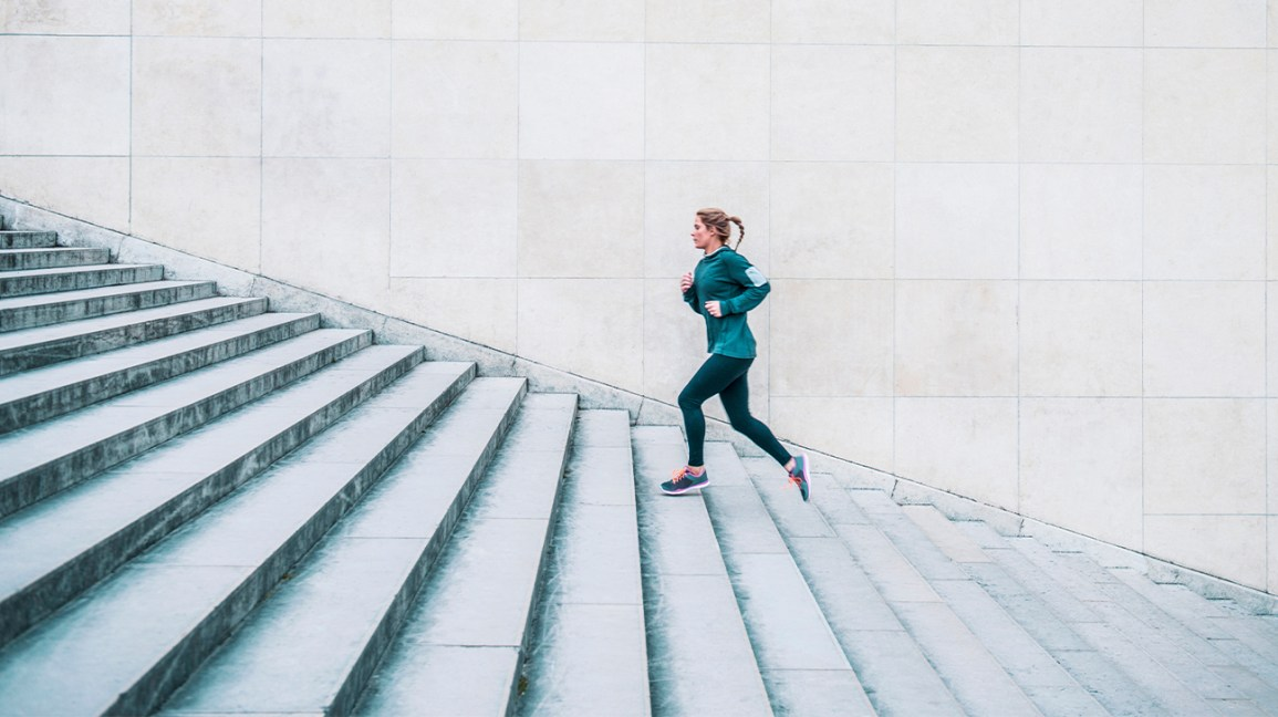 A woman in workout gear does strenuous exercise by running up outdoor stairs.