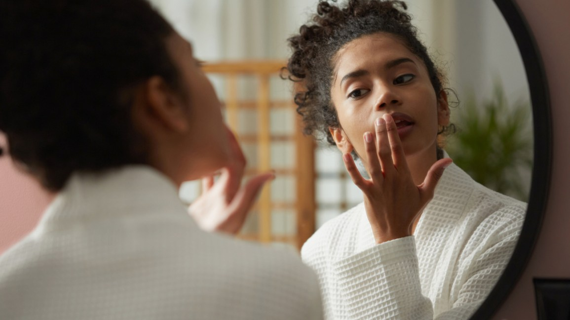 Woman looking in mirror and applying lip balm