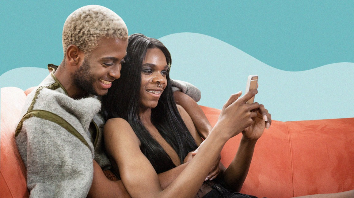 couple sitting together on the couch, one person sitting between the other's legs as they look at their phone