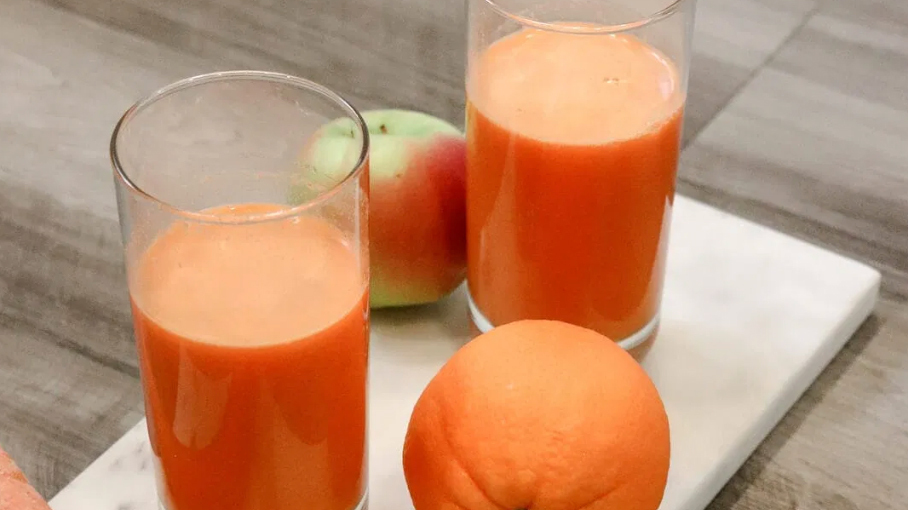 two glasses of orange-colored juice surrounded by an orange and a green apple with red patches
