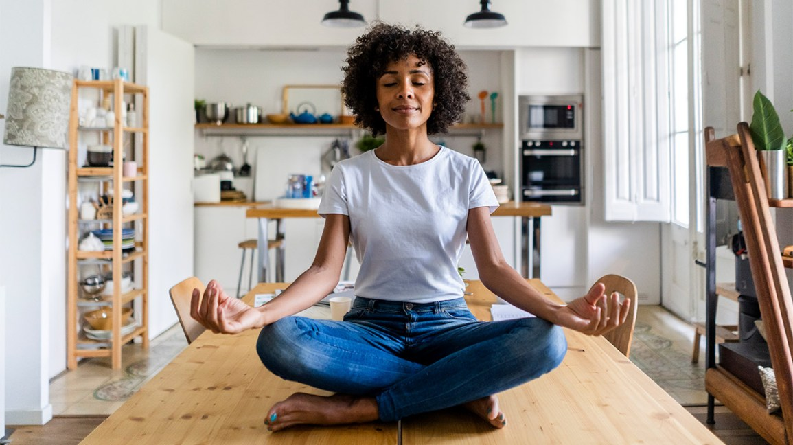 A woman sits cross-legged on a kitchen table while practicing metta meditation, also known as loving kindness meditation.