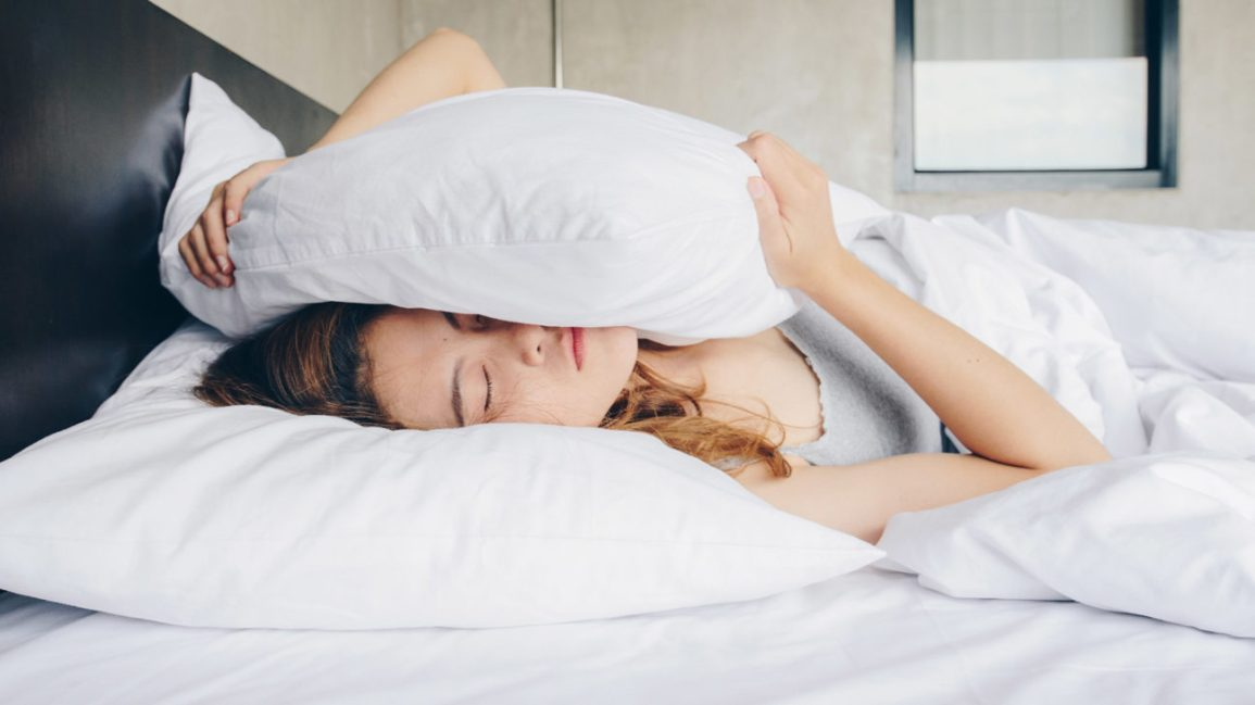 woman experiencing a false awakening with her head under a pillow