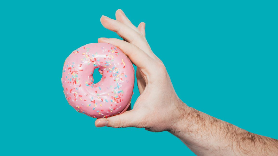 hand holding a donut with pink icing and multicolored sprinkles