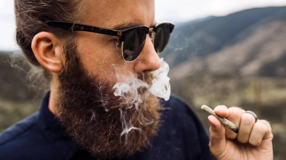gambar yang dipotong dari seseorang dengan jenggot penuh sedang merokok