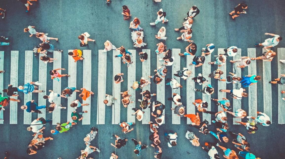 Uma visão geral de uma multidão de pessoas caminhando em uma faixa de pedestres.