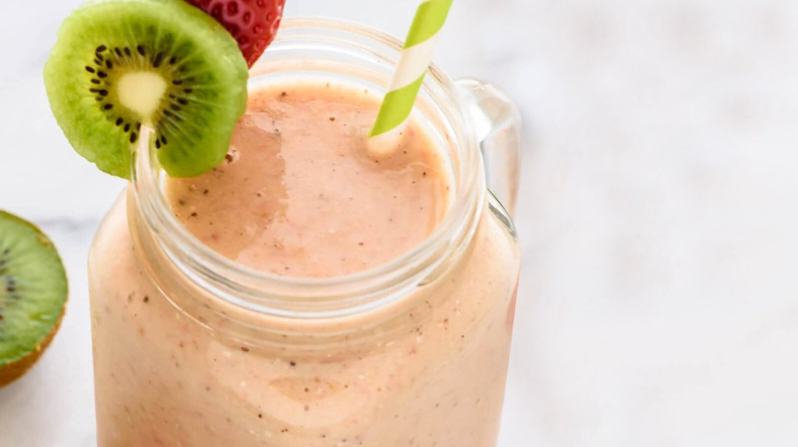 jar containing a pink smoothie topped with a strawberry and slice of kiwi