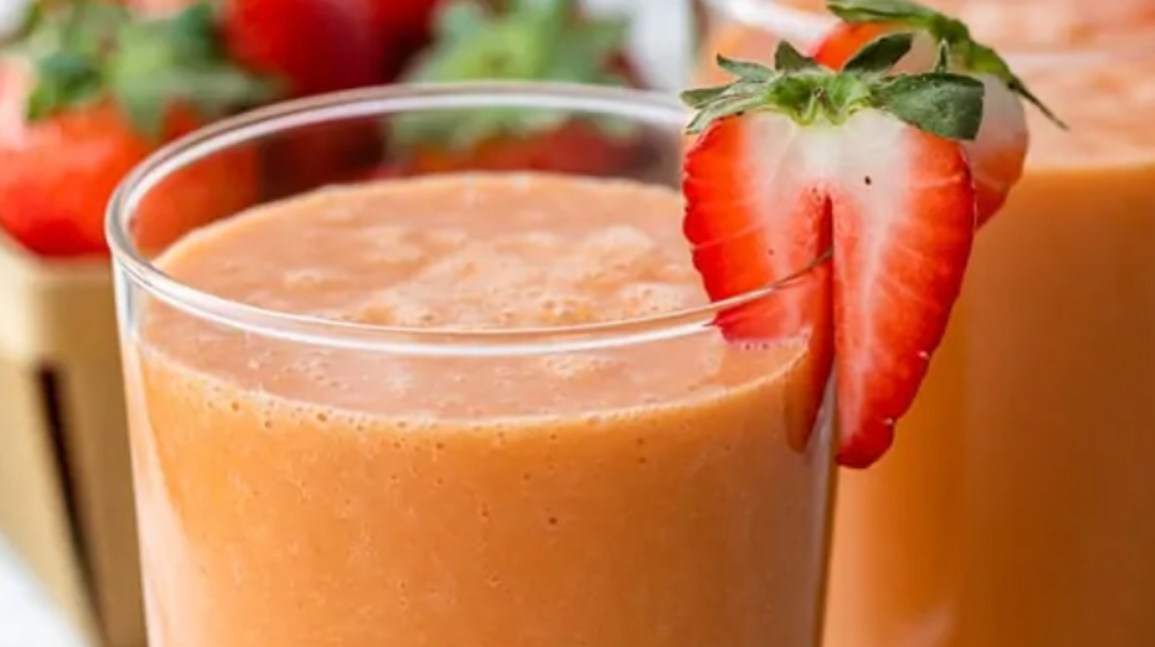 glass of a peach-colored smoothie topped with a strawberry and placed in front a basket of strawberries
