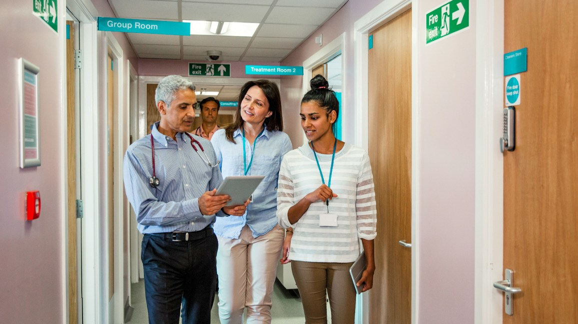 A team of primary care doctors walk down a corridor while reviewing a patient's chart.