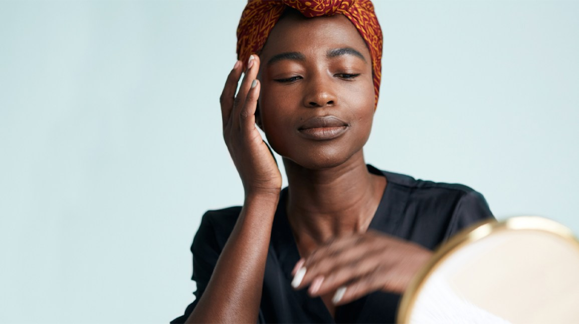 portrait of a black woman wearing a dark orange hair wrap and black v-neck t-shirt gently massaging product into her right cheek