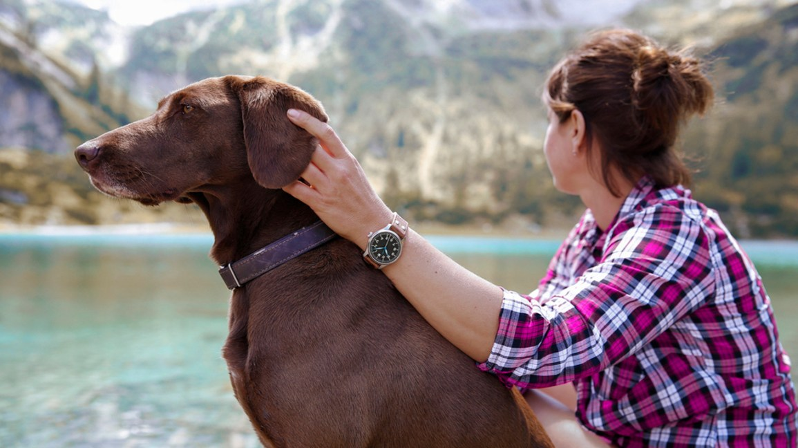 woman sitting with dog looking out at lake