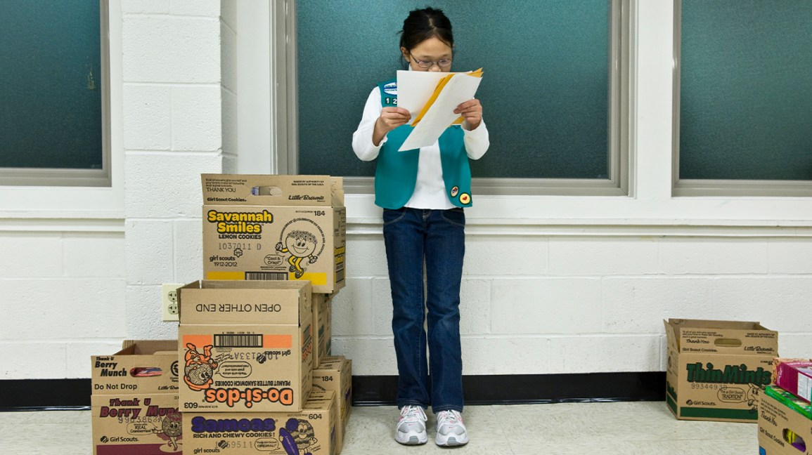 Girl Scout looking over orders near boxes of cookies