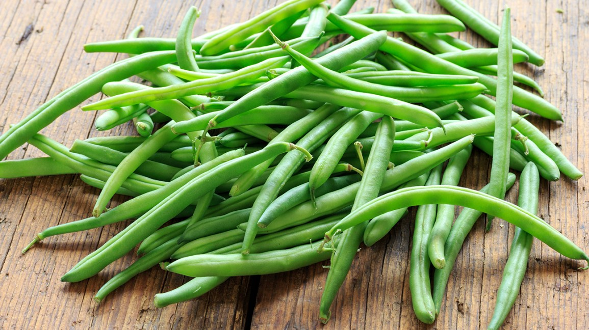 raw green beans on a wooden tabletop