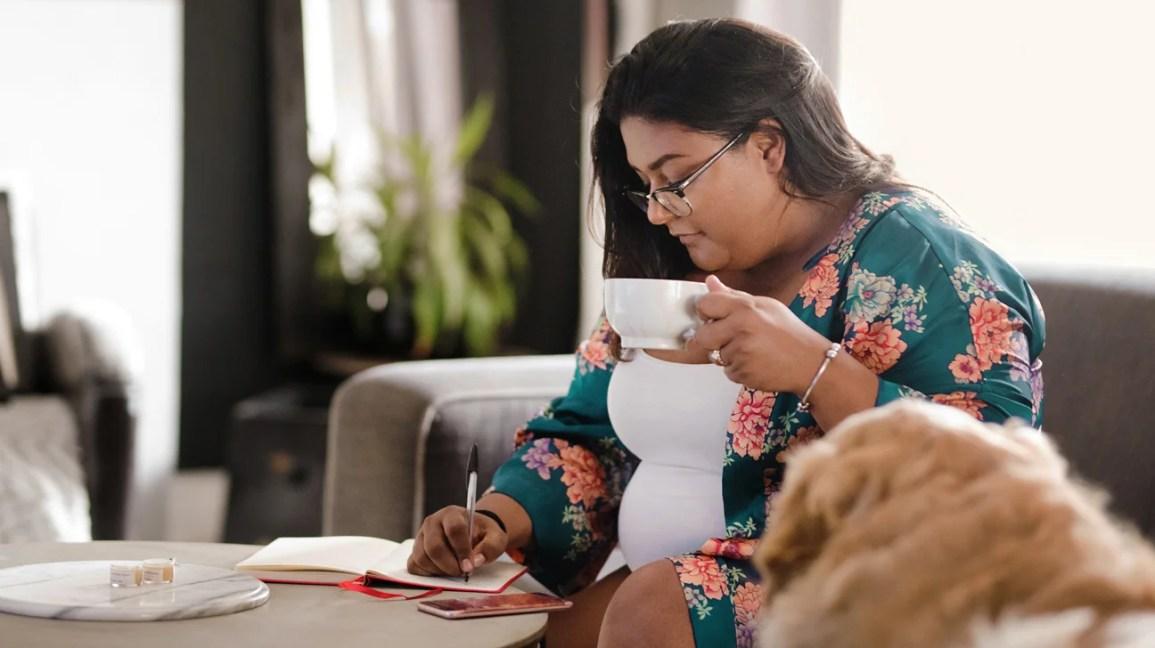 donna che scrive nel diario e beve il tè su un divano