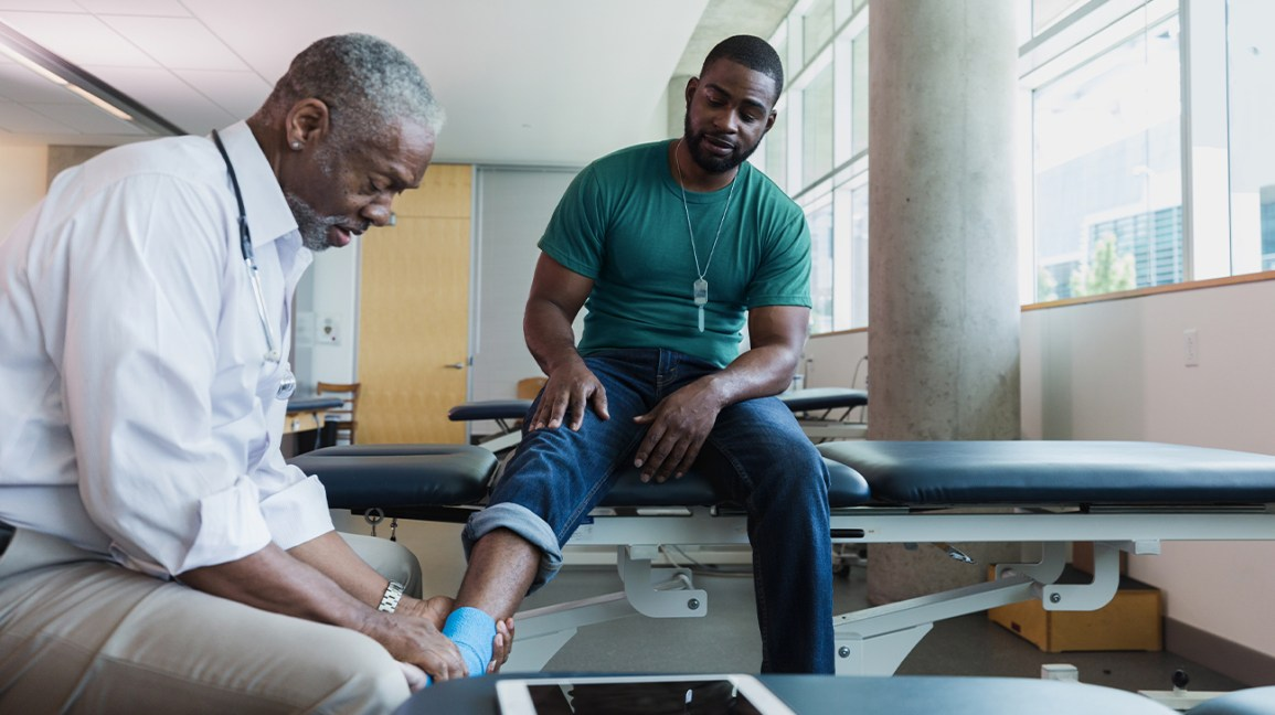 An orthopedic doctor examines the ankle movement of a patient.