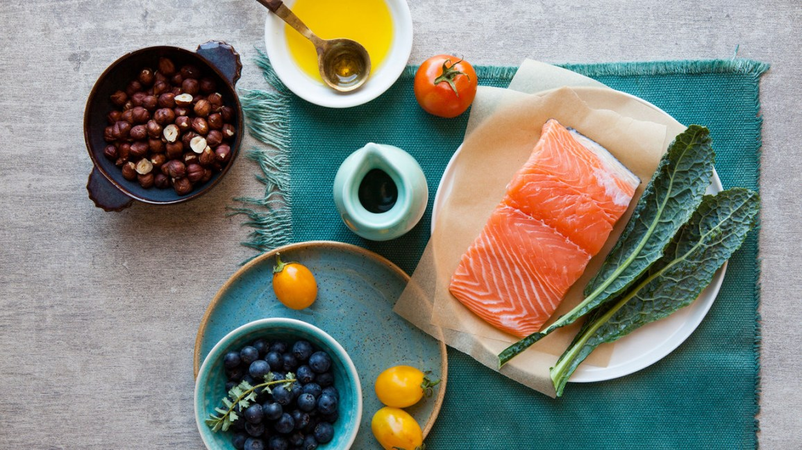 healthy, whole-foods meal with salmon, kale, nuts, berries, and olive oil