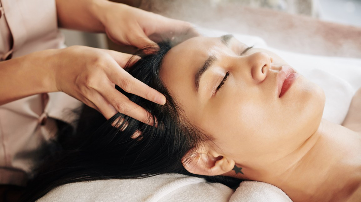 A woman with long dark hair lies on her back while getting a scalp massage.